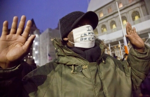 A protester holds up his hands and wears a mask with the words