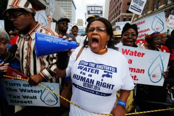 People gather to protest against the mass water shut-offs to Detroit citizens behind in their payments during a demonstration in downtown Detroit